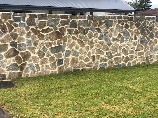 Exterior house wall using Aussietecture Tilpa granite stone walling with a lawn