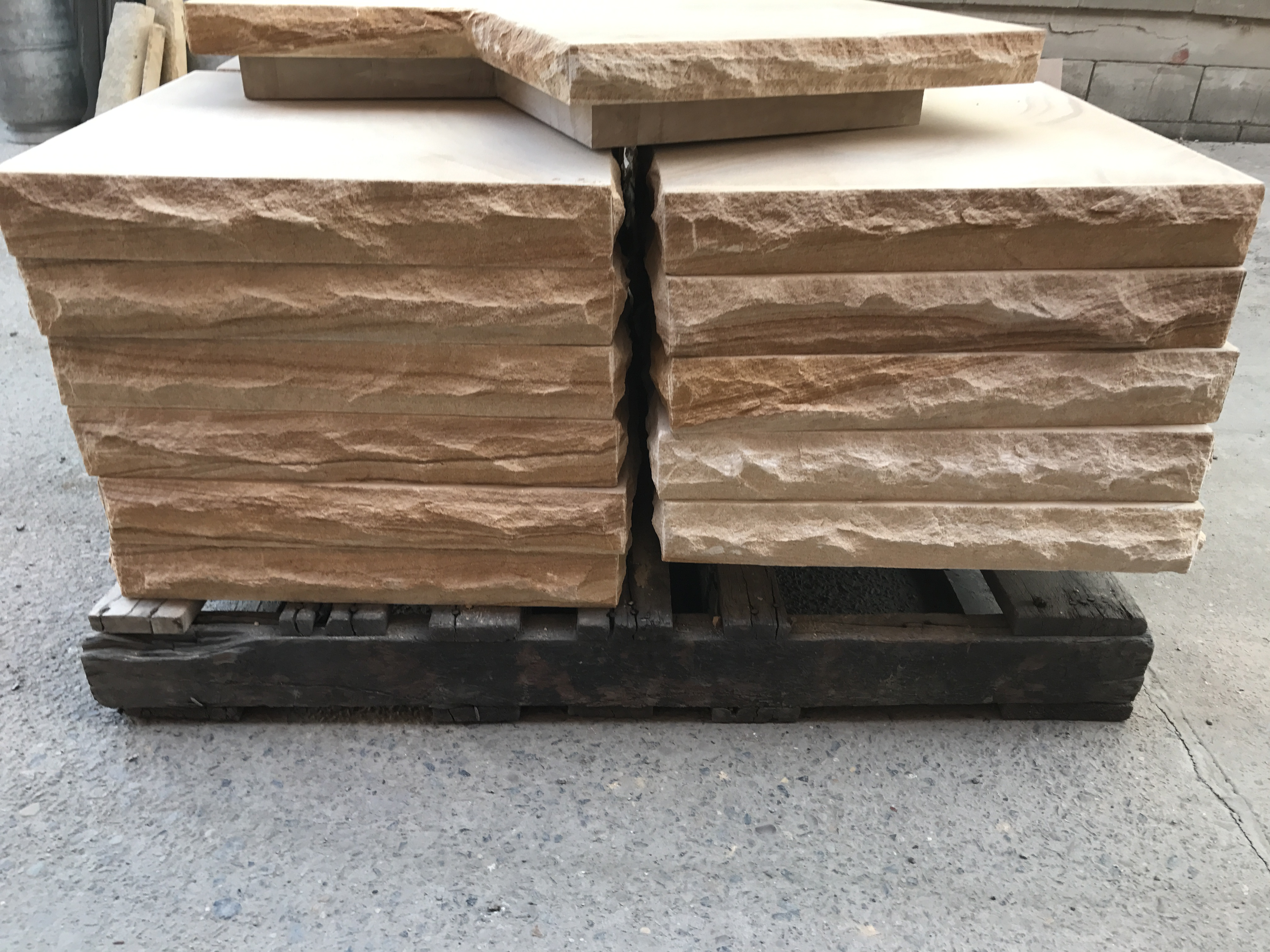 A pack of sandstone caps in a pallet, rock face on all sides