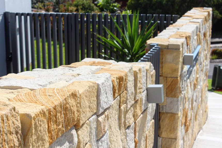 a house garden with a stone wall, natural stone wall cladding, metal gate and plant