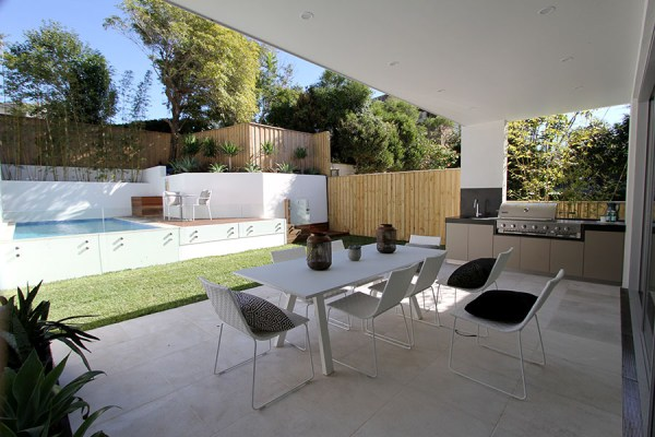 Back yard with a swimming pool and outdoor barbeque place paved with Cattai marble paving