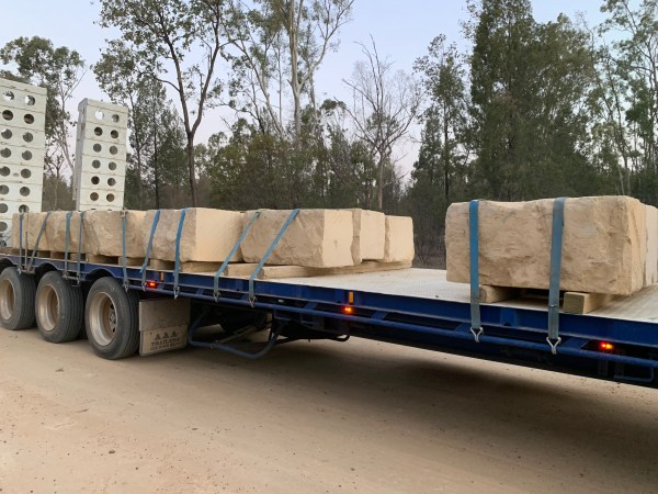 Sandstone quarry blocks and log is being delivered to a residential construction site