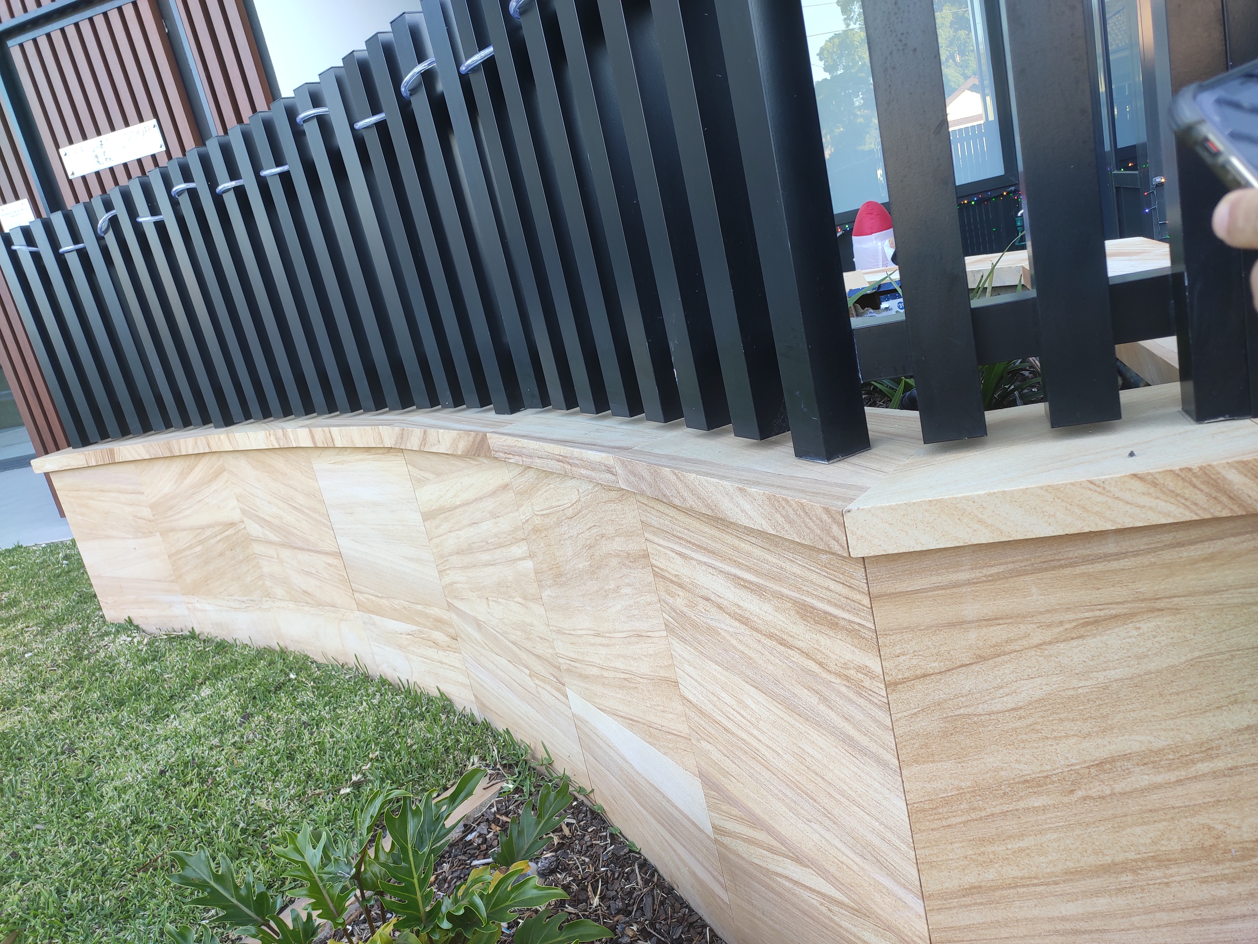 Sandstone tiles and capping in a house garden fence