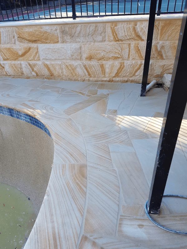 Banded Sandstone Crazy paving seen in swimming pool flooring and rockface as claddings