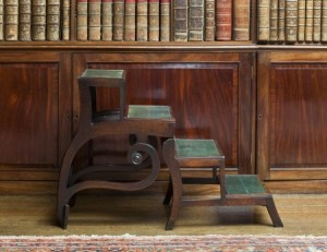 "Regency mahogany library steps which fold up to form a sabre-leg armchair - the ""Patent Metamorphic Library Chair"" by Morgan and Sanders, in the Library at Saltram, Devon."