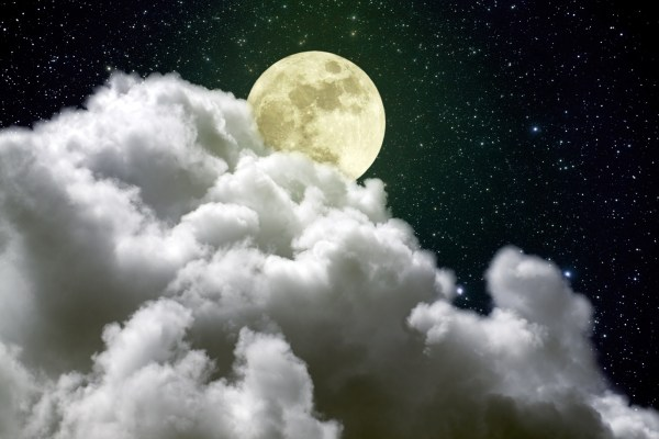 Beautiful full moon rising over a big white cloud in a beautiful cloudy night