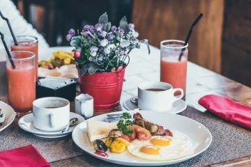Breakfast with fried eggs, juice, coffee and fruits on wooden table in the tropical restaurant, Bali island.