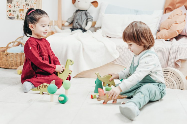Two Children Sitting Down Playing With Toys