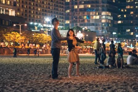 A Korean couple sets off fireworks at Haeundae Beach at night