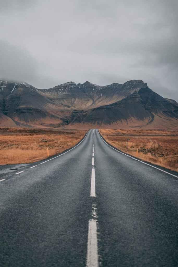 empty highway overlooking mountain under dark skies