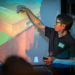 man with beer in front of projector screen