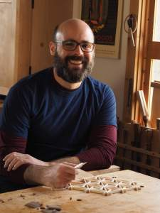 woodworker with glasses in front of workbench