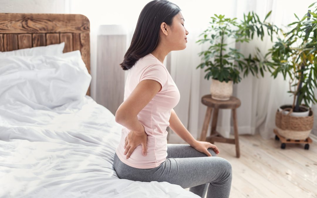 Young Lady Suffering From Pain In Lower Back Sitting On Bed At Home