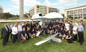 Chief of Air Force AIRMSHL Geoff Brown, Northrop Grumman Australia CEO Ian Irving, and students of Canberra's Dickson College pose in front of a full-scale mock-up of the company's MQ-4C Triton in Canberra. (Northrop Grumman)