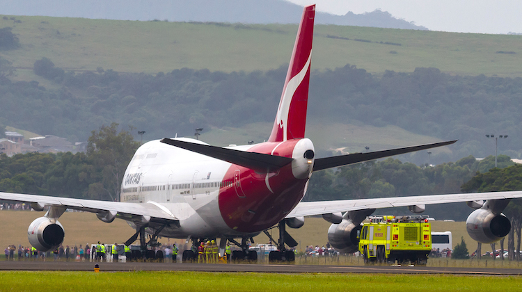 Airservices fire fighters inspect the wheel brakes of a Qantas 747-400 shortly after landing at Illawarra Regional Airport. (Seth Jaworski/Airservices)