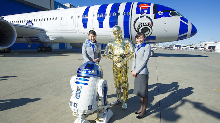 ANA staff with Star Wars characters and the 787-9 R2-D2 themed Dreamliner in the background. (ANA/Boeing)