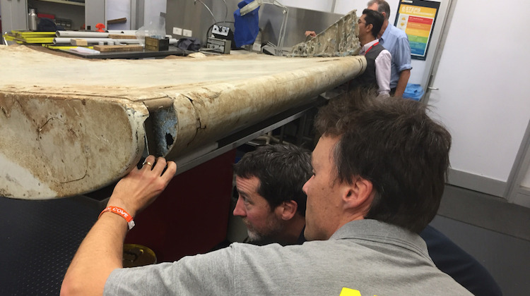 A supplied image of ATSB investigators looking at a wing flap believed to be from MH370. (ATSB)