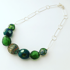 Flame worked glass beaded necklace by Jemma Clements. Green hues on sterling silver chain.