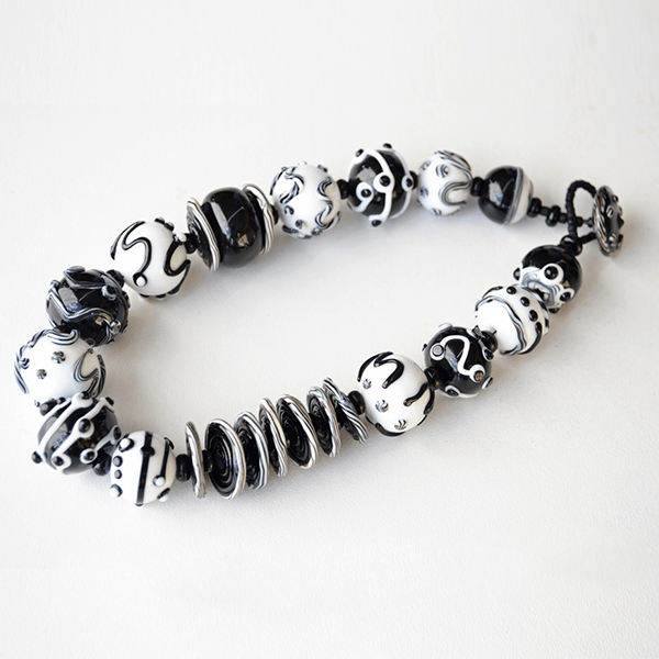 Black and White Hollows series necklace by Su Bishop. Round beads 2,3cm D. L44cm. Glass button and beaded loop
