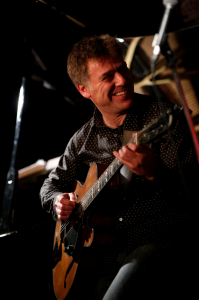 Peter Bernstein smiling with guitar. Photo by Tarn Dunn