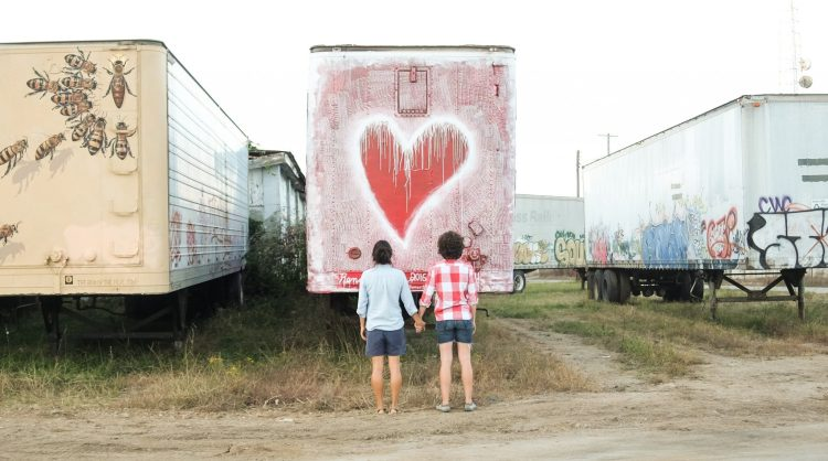 Erin McGrady and Caroline Whatley holding hands in Asheville, NC's River Arts District.