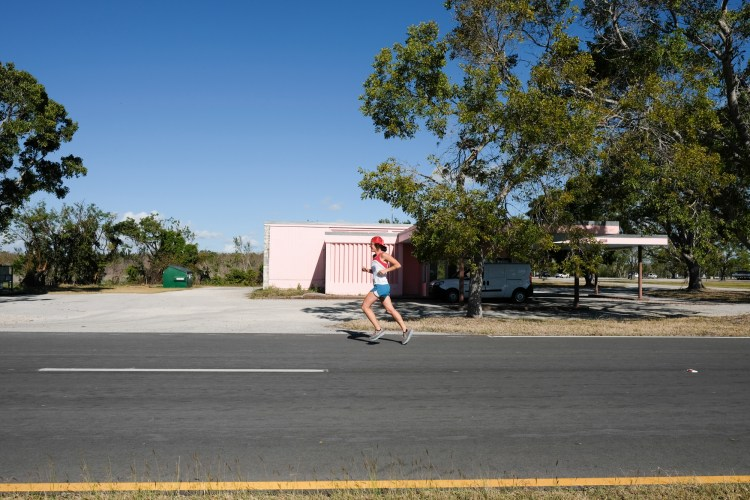 Woman running on the road in the Everglades.