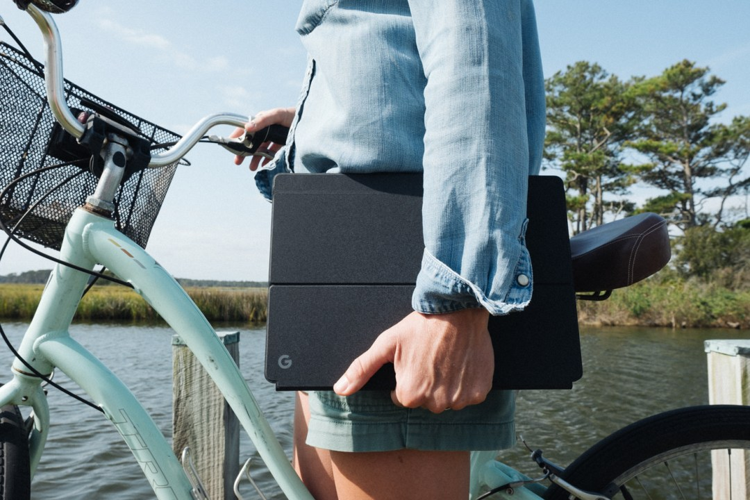 person holding the Google Pixel Slate near the water.