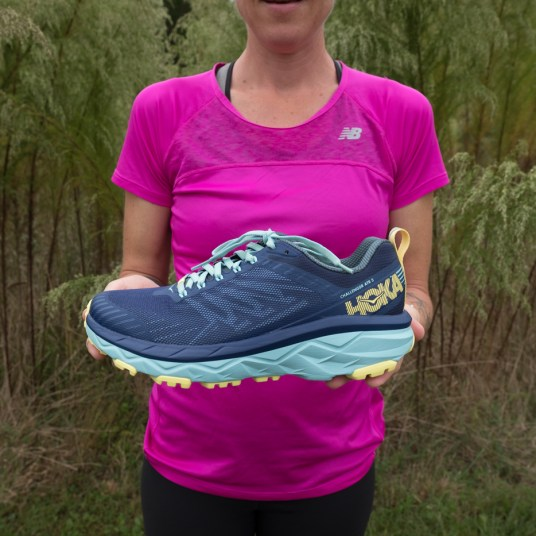 Caroline Whatley holding up the outside view of the Women's Hoka One One Challenger ATR 5