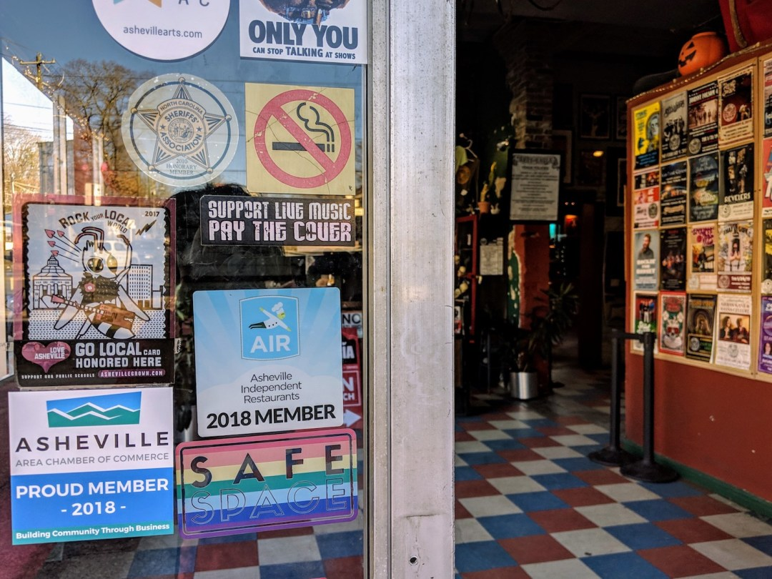 Doors to the Grey Eagle in Asheville with stickers on it that include No Smoking, an LGBTQ Safe Space and  proud member of the Asheville Area Chamber of Commerce.