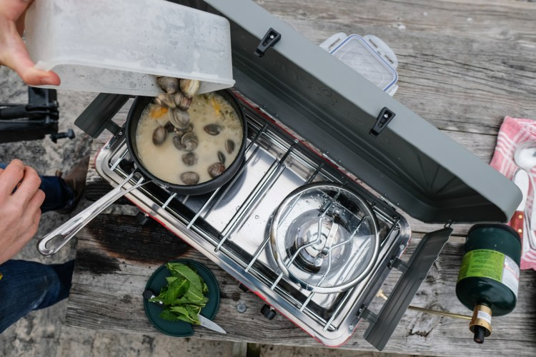 Photo of someone living van life cooking outside on a grill during the coronavirus pandemic.
