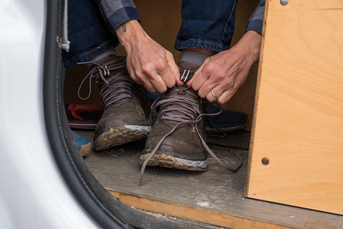 photo of a woman lacing up the Hoka One One Women's Challenger Mid hiking boot.
