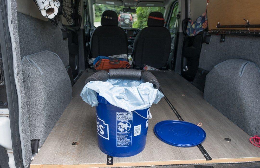 a photo of the inside of a small Ram Promaster City camper van and a DIY camper van toilet made out of a blue 5-gallon bucket with a Wag Bag and pipe insulation.