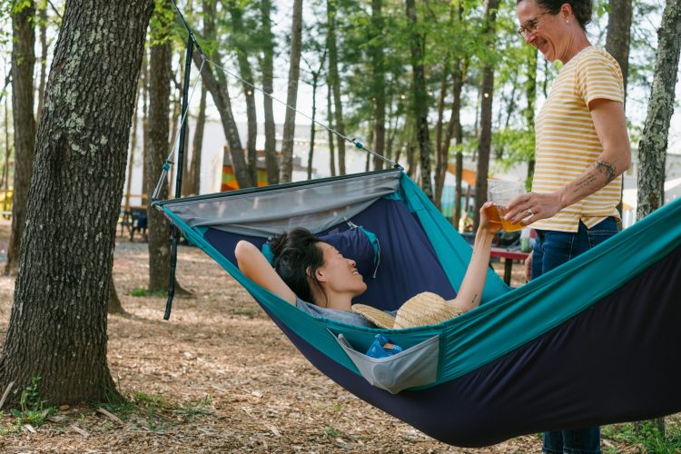 Erin McGrady is laying in a blue hammock toasting Caroline Whatley with a beer. Highland Brewing Company's shipping containers are in the background.