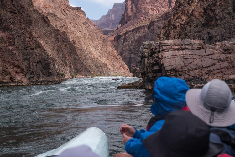 a raft coming through a rapid in the Grand Canyon. People in rain gear are blurred out in the foreground.