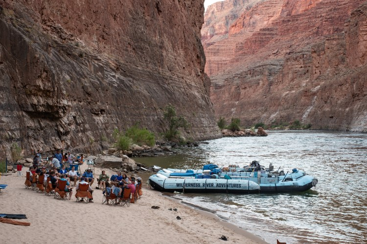 About 20 people are circled up on the sand in red chairs. The blue rafts are anchored nearby in the water. The Grand Canyon walls are pink and red in the background and the time of day is early evening.