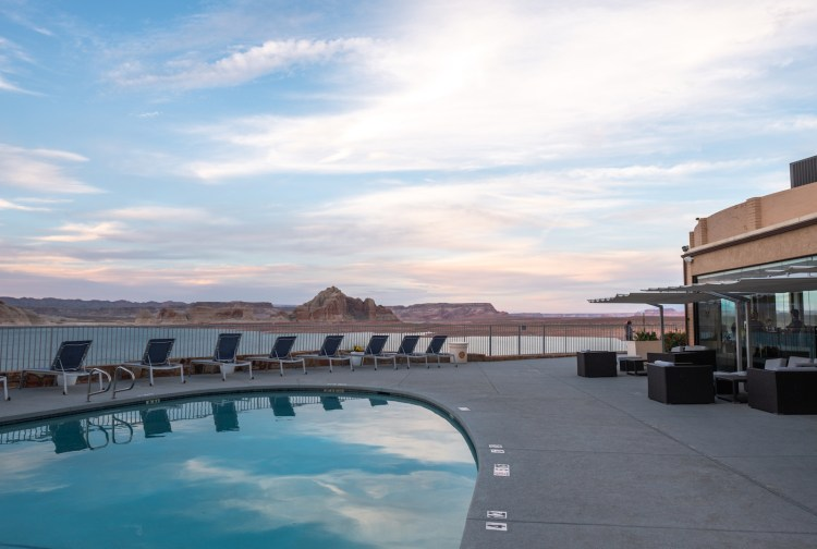 A blue pool with clouds reflected in the water is in the lower left hand corner of the photos. Lake Powell is in the background. It's sunset.