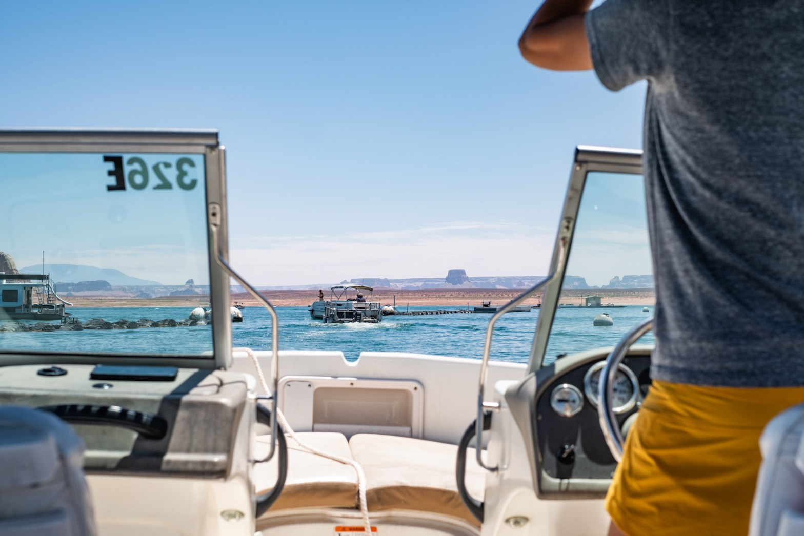 Erin McGrady is standing in a grey shirt and yellow shorts and driving a white powerboat on Lake Powell. A boat is in the distance on the lake.
