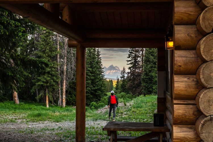 Erin McGrady walks outside the cabin with a camera in hand. The Grand Tetons are in the distance. The cabin and it's wooden slats are in the right hand side of the photo. The porch light on the cabin is on.