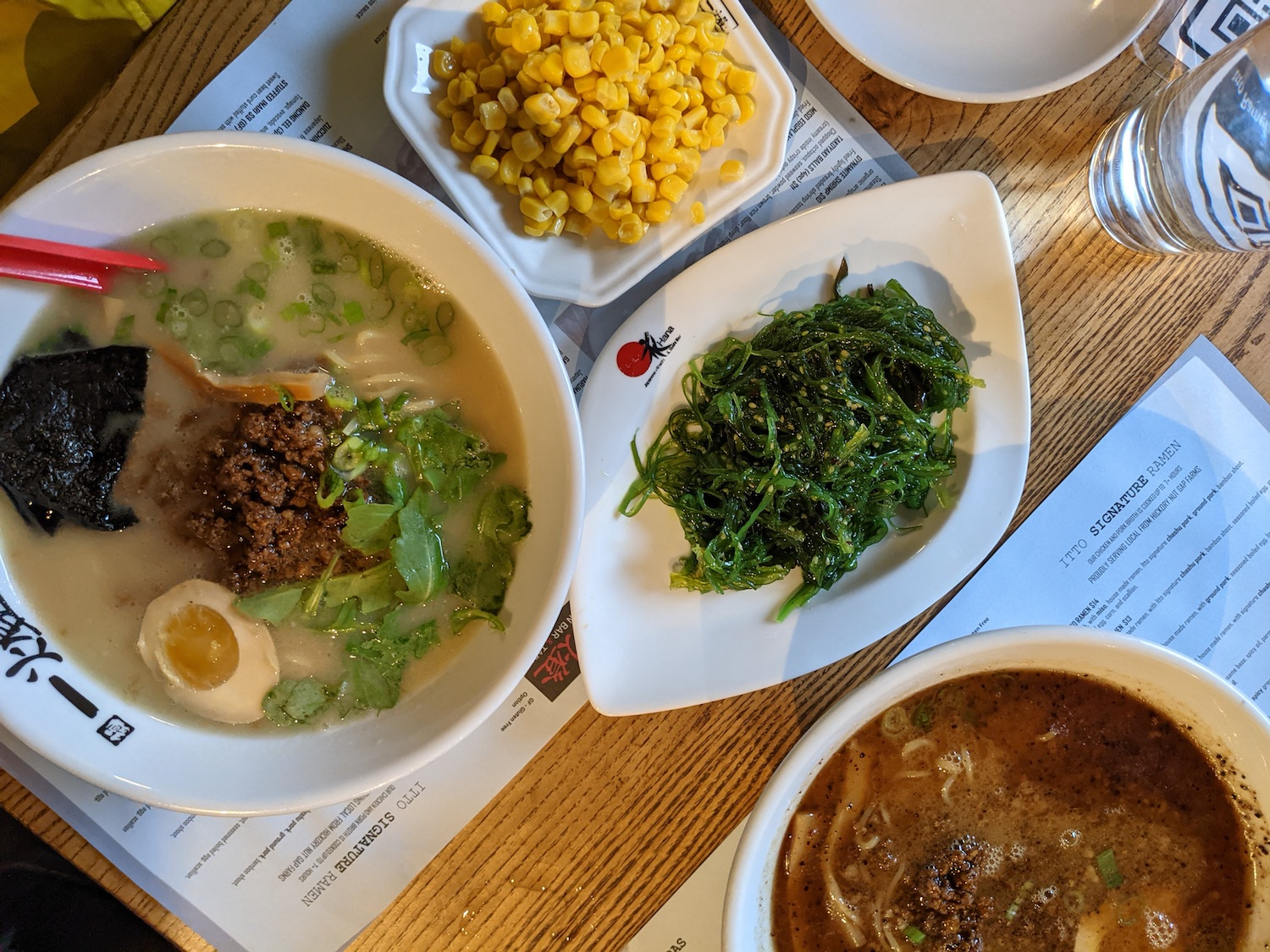 a flat lay photo of the Classic Ramen, seaweed salad, Deluxe Ramen, and a side of corn at Itto Ramen in West Asheville. The food is on a wooden table and the paper menus are underneath the plates and bowls.