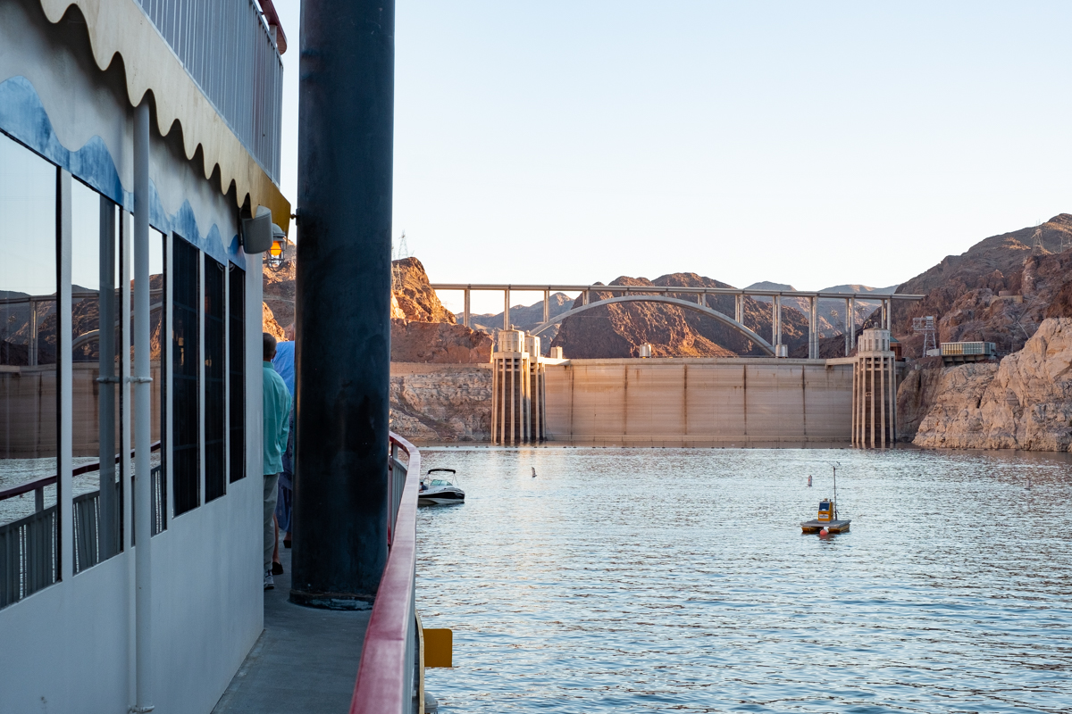 Hoover Dam is bathed in golden sunlight. The Desert Princess is on on the left hand side of the photo and a small boat and two buoys are in the water.