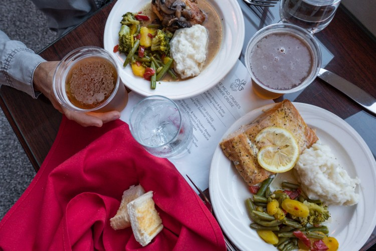 A flatlay photo of the dinner on the Desert Princess on Lake Mead. A woman's hand holds a beer in a cup and two pieces of garlic bread are wrapped in a red napkin. There is a salmon filet with a lemon slice on top of one of the plates as well as a scoop of mashed potatoes and mixed vegetables. The other plate has chicken with mushrooms and gravy, mashed potatoes and mixed vegetables.