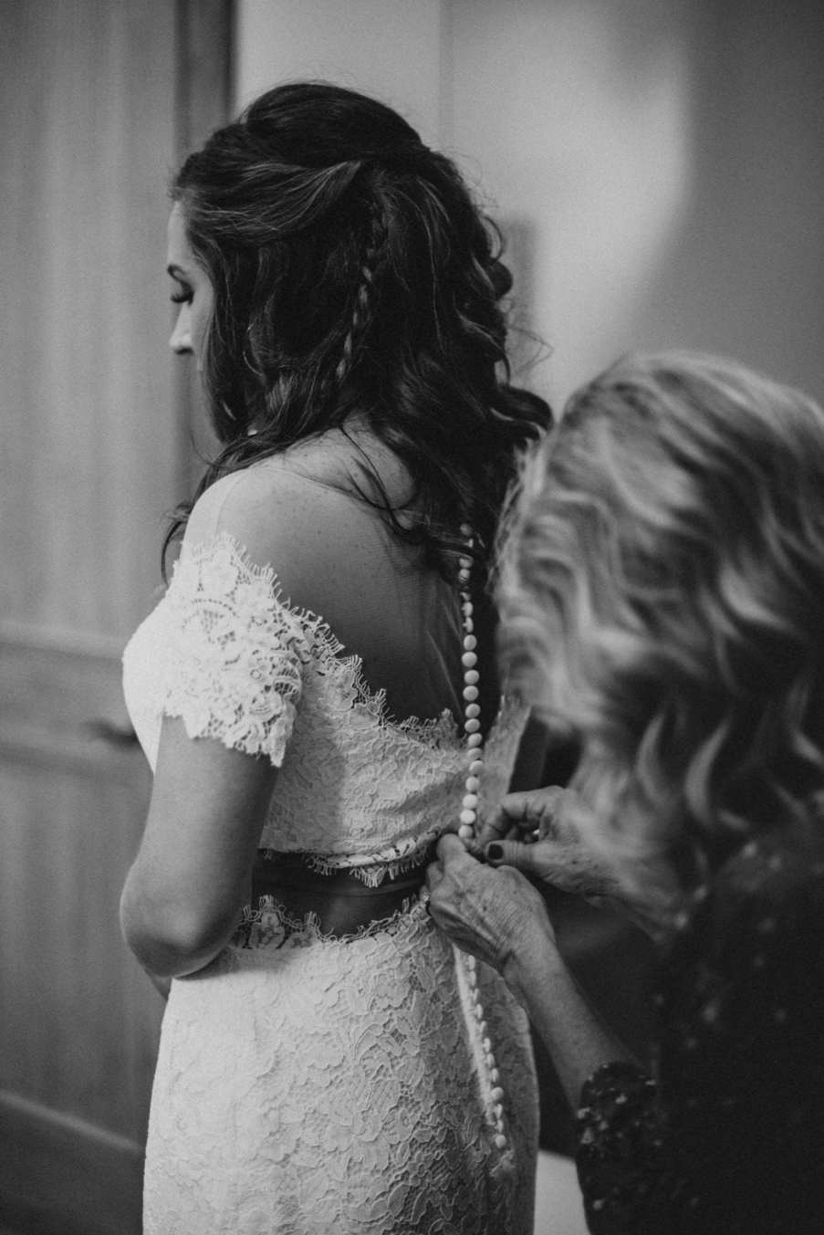 Mother buttoning up Bride's wedding dress