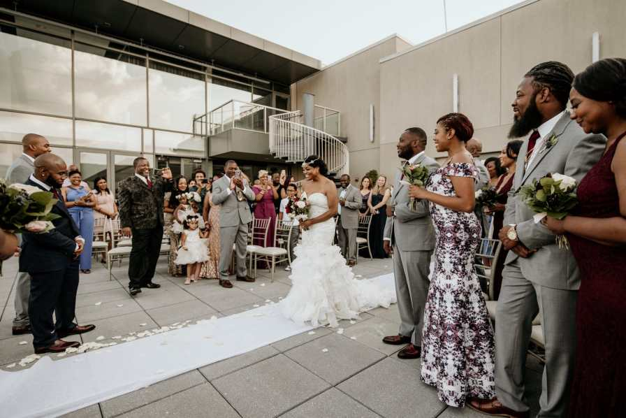 Bride beaming with joy walking down the aisle