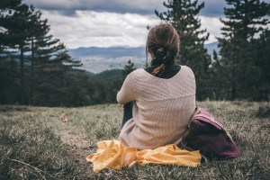 Photo of a woman from behind sitting on a blanket on a hill and looking at the mountains in the distance. She feels at peace after seeking PTSD treatment. She used EMDR therapy in Castle Rock, CO to help her recover from traumatic events. | 80109 | 80108 | 80104