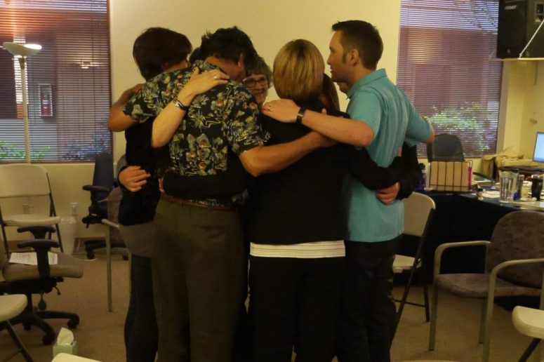 A group of people huddle together standing in a circle with their arms around one another.