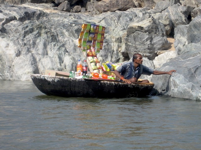 Man selling snacks in Coracle in Hogenekkal