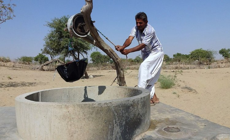 Man taking water from a well in desert