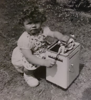 photo of toddler Debbie with toy washing machine