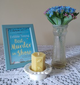 arrangement of book cover, candle and vase