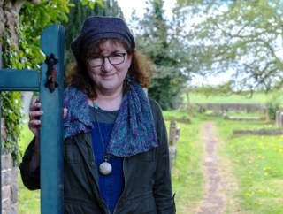 head and shoulders photo of Debbie at churchyard gate with graveyard behind