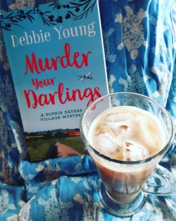 image of a glass of iced coffee with a copy of Murder Your Darlings against a blue cotton sarong